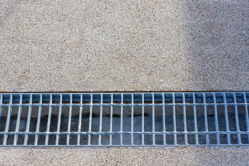 Chiuda sullo scolo della griglia della fogna intorno alla via o al passaggio pedonale fotografia stock