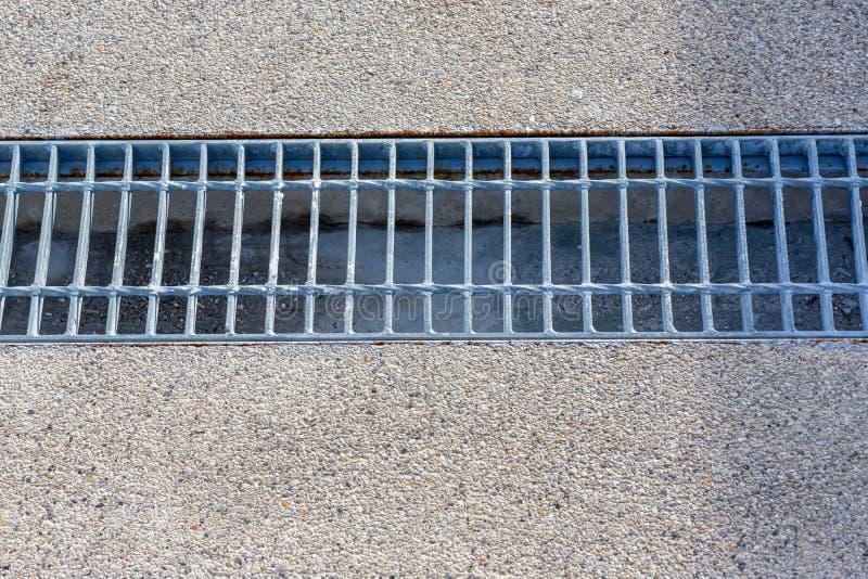 Chiuda sullo scolo della griglia della fogna intorno alla via o al passaggio pedonale immagini stock