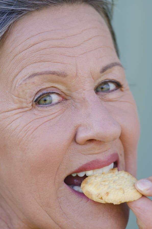 Chiuda sullo spuntino dolce mordace del biscotto della donna felice immagine stock libera da diritti