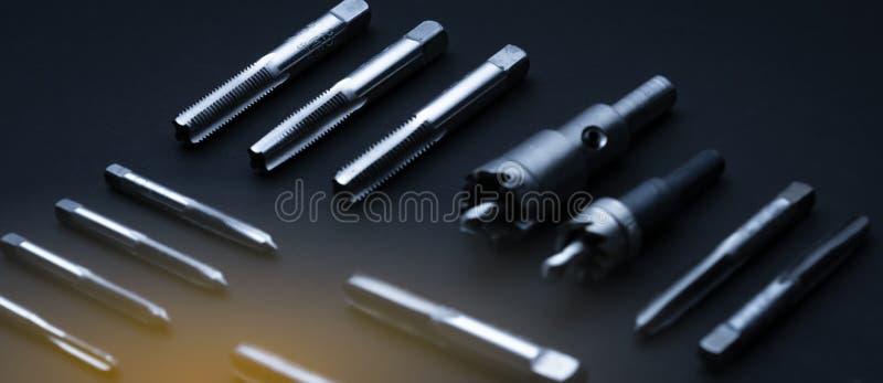 Chiudere la punta del rubinetto del flauto rettilineo e la sega del foro sullo sfondo scuro Apparecchiature di maschiatura indust fotografia stock