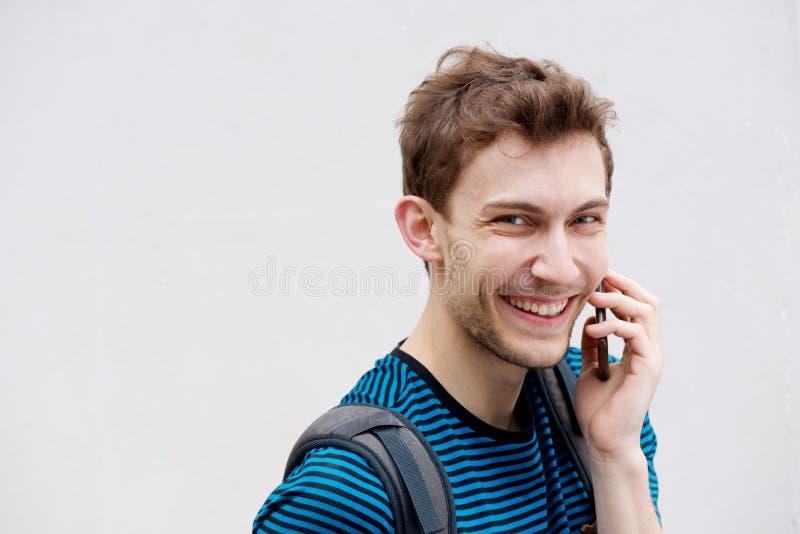 Chiudi il giovane che parla con il cellulare e ridi su sfondo bianco fotografia stock libera da diritti