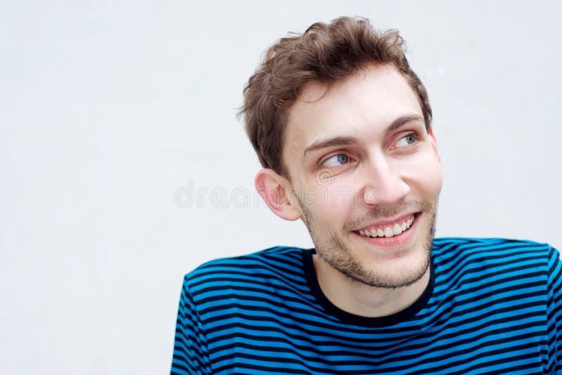 Chiudi il giovane sorridendo e guardandolo lontano da uno sfondo bianco isolato fotografia stock libera da diritti