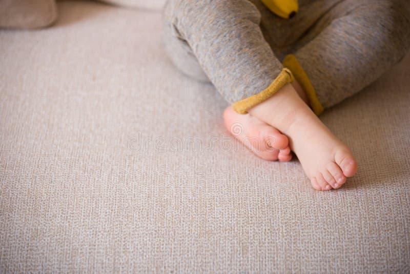Chiudi le gambe per bambini Piedi per bambini sul divano Barefoot immagini stock