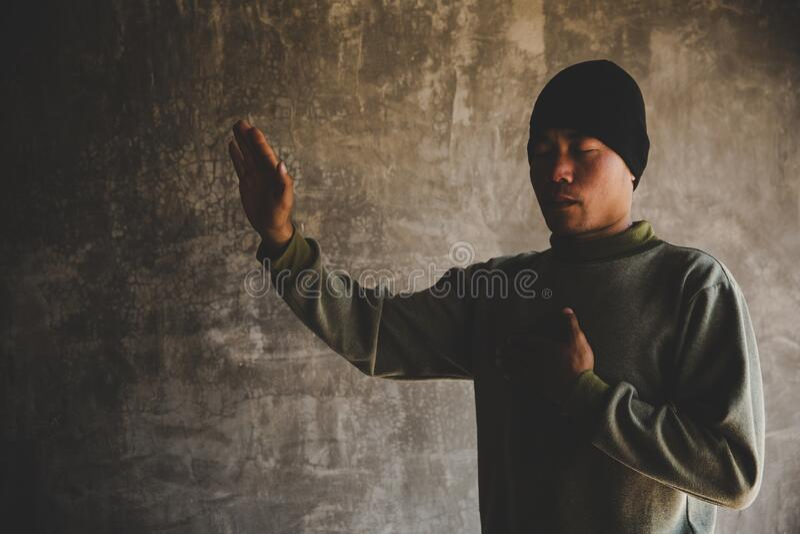 Chiuso il ritratto di un uomo che pregava con gli occhi immagine stock