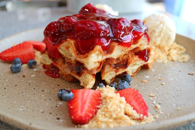 Chiuso su un piatto della cialda con la salsa della fragola, le bacche fresche ed il gelato alla vaniglia immagini stock