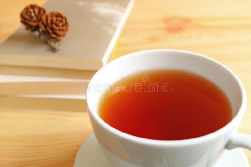 Chiuso su una tazza di tè caldo sulla tavola di legno con la pila vaga di libri e delle pigne asciutte sulla cima nel fondo immagini stock