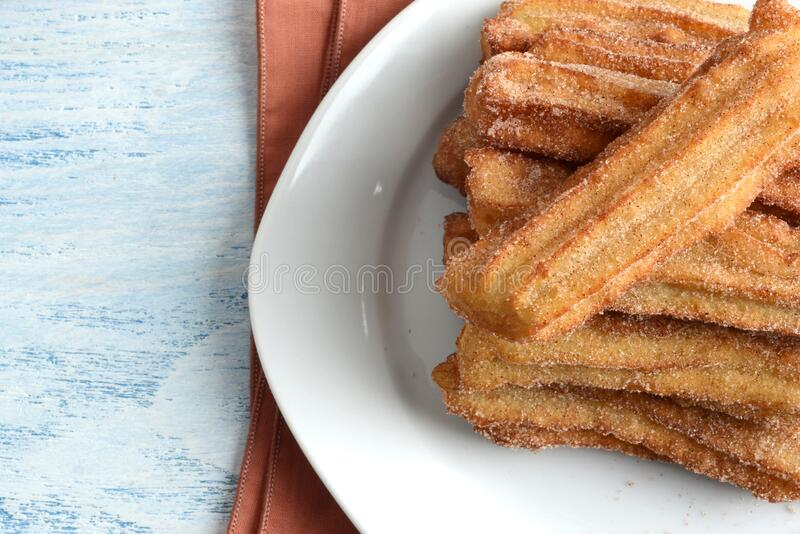 Chiusura dei churros di cannella in alto su un piatto immagine stock