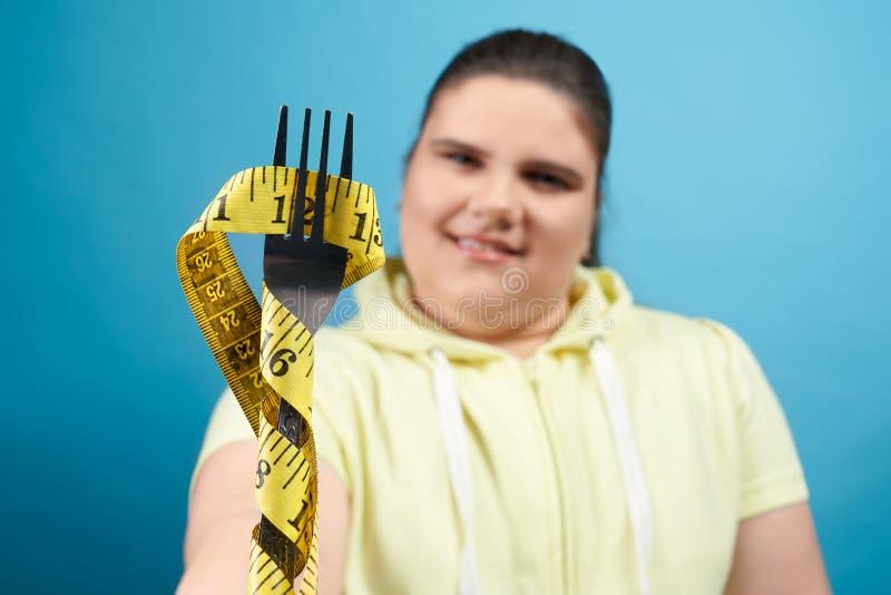 Chiusura della forchetta avvolta da un nastro di misura che tiene per ragazza immagine stock