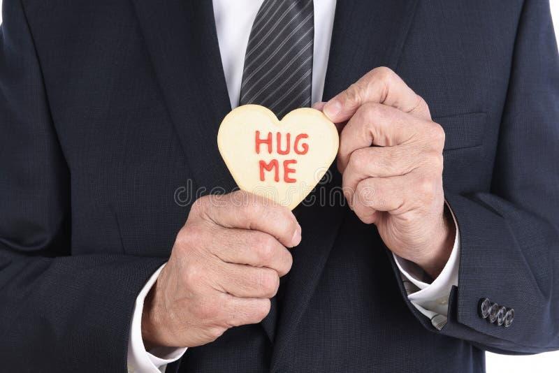 Chiusura di un uomo d'affari con in mano un biscotto a forma di cuore con le parole Hug Me scritto in ghiaccio rosso L'uomo è irr immagini stock libere da diritti