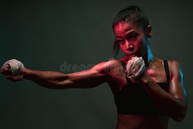 Chiusura di una donna asiatica, ombre di una donna di buona salute che si aggira per l'allenamento di pugilato con un muscolo con fotografie stock