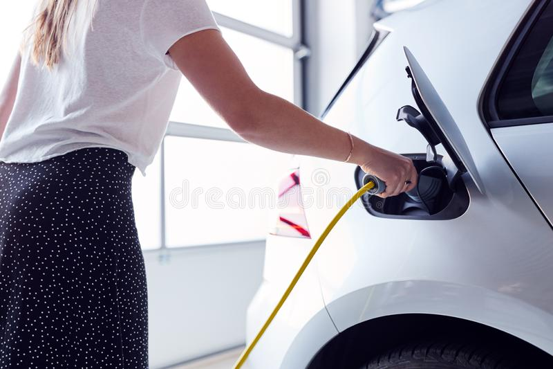 Chiusura Di Una Donna Che Carica Veicoli Elettrici Con Cavo In Garage A Casa fotografia stock libera da diritti