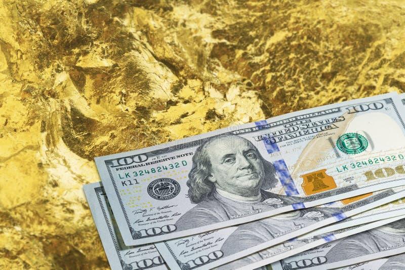 Chiusura di una miniera d'oro per una valanga di banconote da cento dollari Industria mineraria con dollari e oro fotografia stock