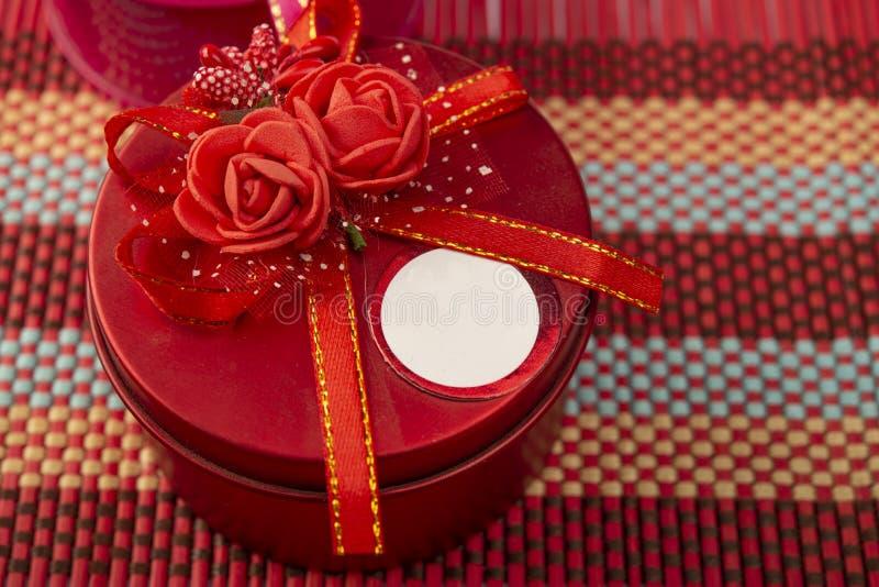 Chiusura di una scatola regalo rossa con fiori in cima immagine stock