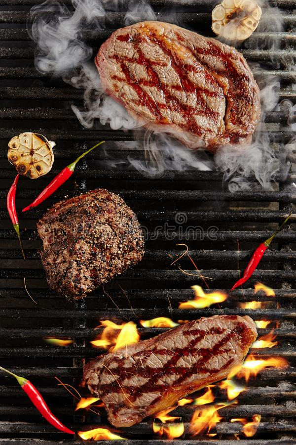 Chivas Beef Steak, Pepper Steak and Smoked Ribeye Steak. Hot Juicy Chivas Beef Steak on Barbecue Flames Grill Background. Smoked Ribeye Beef Steaks with Grilled stock images