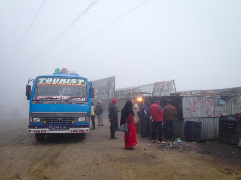 Chiya stop. Dumre, Nepal - 5 February 2014: A long-distance bus from Pokhara to Nepalgunj makes an early morning tea stop in the fog at roadside stalls near royalty free stock image