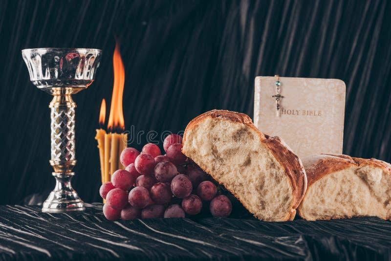 chleb, biblia, chalice i chrześcijanin, krzyżujemy na czerń stole, zdjęcia royalty free