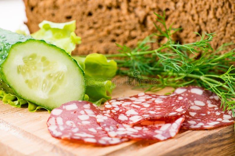Chleb i kanapka z salami i świeżym ogórkiem obraz stock