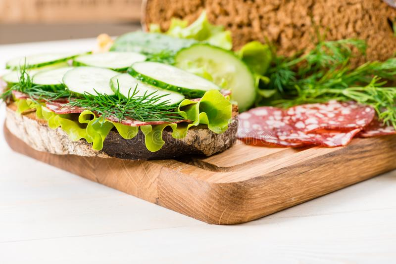 Chleb i kanapka z salami i świeżym ogórkiem zdjęcia stock