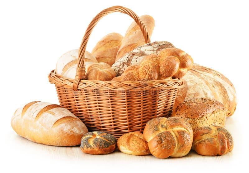 Chleb i rolki w łozinowym koszu odizolowywającym na bielu obraz stock