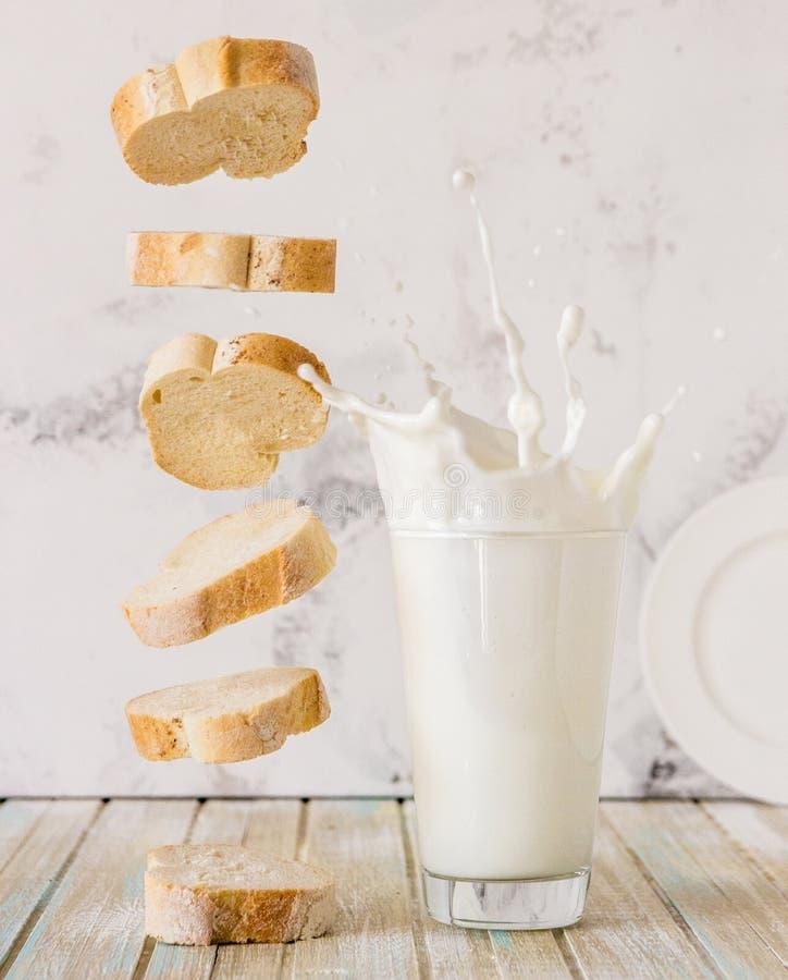 chleb mleka Latający baguette i mleko bryzgamy w szkle obraz stock
