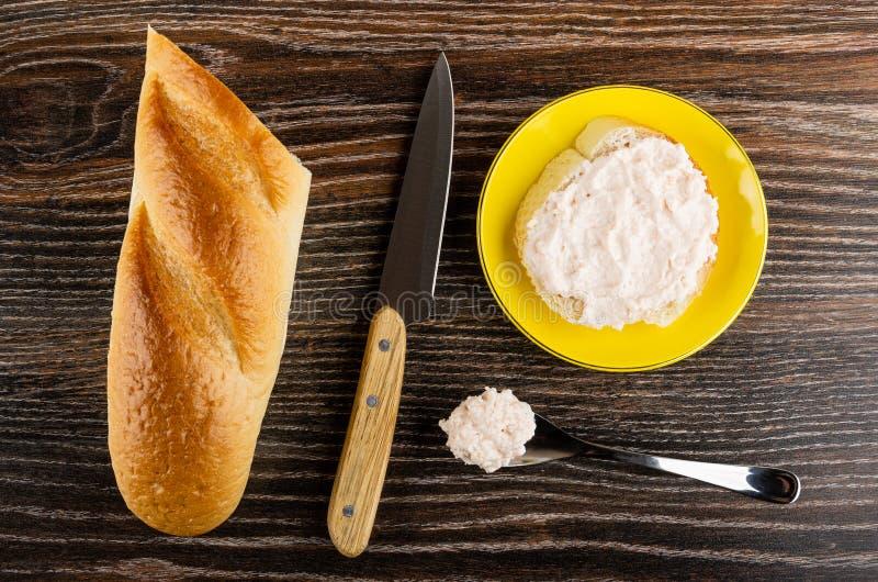 Chleb, nóż, kanapka z krill pastą w spodeczku, łyżka z pastą na drewnianym stole Odg?rny widok obraz royalty free