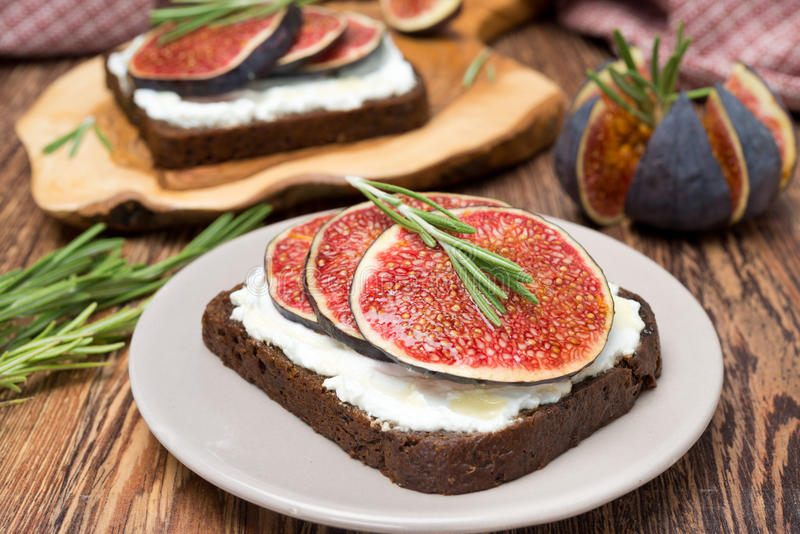 Chleb z koźlim serem, figami, miodem i rozmarynami na talerzu, zdjęcie royalty free