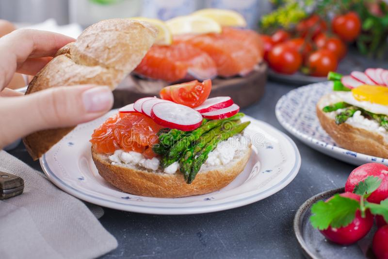 Chleb z serem, rzodkwią, łososiem i asparagusem, w kobiety ` s ręce Różny Zdrowy łasowanie Wyśmienicie śniadanie dla rodziny obraz stock