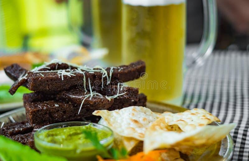Chlebowi croutons przekąszają z czosnkiem i szkłem piwo na stole w barze obrazy stock