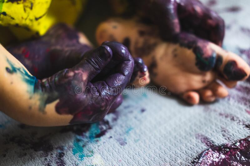 Little kid hands and feet covered with multiple colours. Chlid playing with different color paintings ends with multicolor hands and feet stock photos