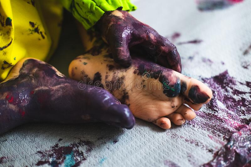 Little kid hands and feet covered with multiple colours. Chlid playing with different color paintings ends with multicolor hands and feet stock photography