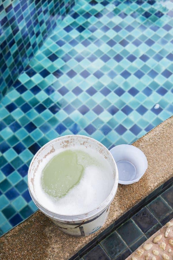 Chlore dans le récipient en plastique blanc sur le bord de piscine photos stock