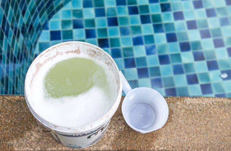 Chlore dans le réservoir chimique sur le bord de piscine photos stock