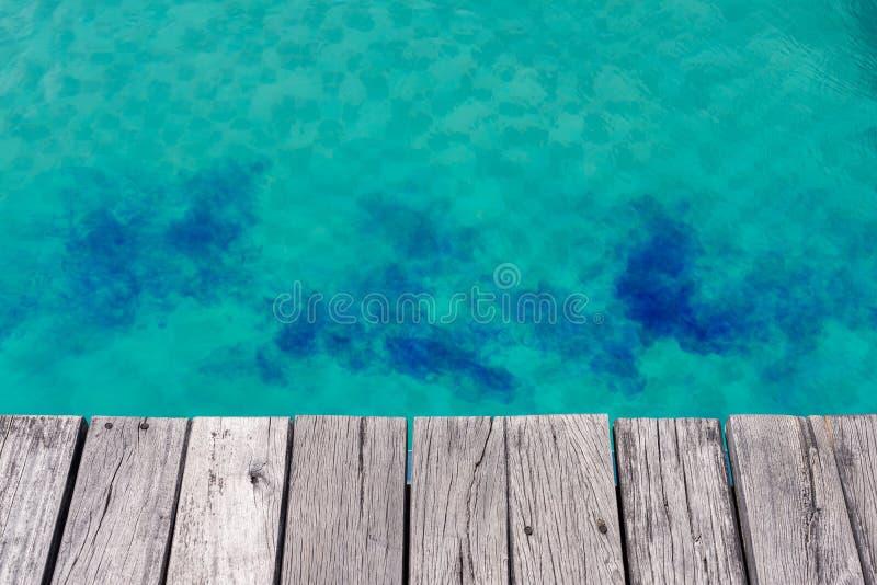 Chlore liquide bleu dans la piscine verte avec le bord en bois de planche image libre de droits