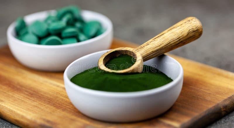 Chlorella, spirulina zielone algi w proszku i pastylki formy zbliżenie, makro- strzał obraz stock
