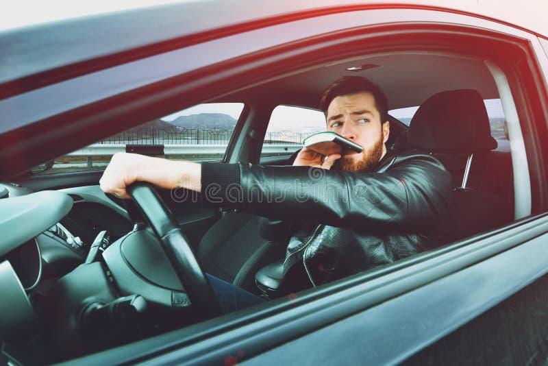 Chmielny mężczyzna jedzie samochód z butelką alkohol w jego ręce Obsługuje whisky od żelaznej kolby za kołem samochód zdjęcie royalty free