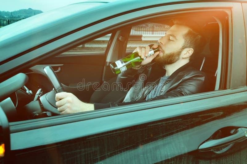 Chmielny mężczyzna jedzie samochód z butelką alkohol w jego ręce Mężczyzna pije piwo przy kołem samochód zdjęcia royalty free