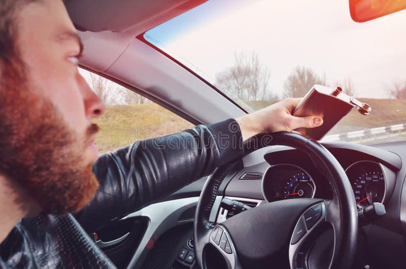 Chmielny mężczyzna jedzie samochód z butelką alkohol w jego ręce Mężczyzna trzyma kolbę whisky obraz stock