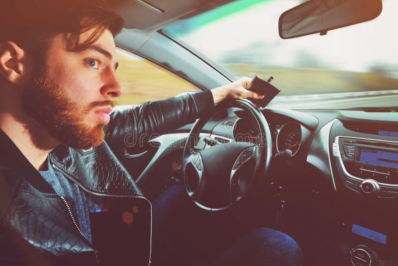 Chmielny mężczyzna jedzie samochód z butelką alkohol w jego ręce Mężczyzna trzyma kolbę whisky obrazy stock