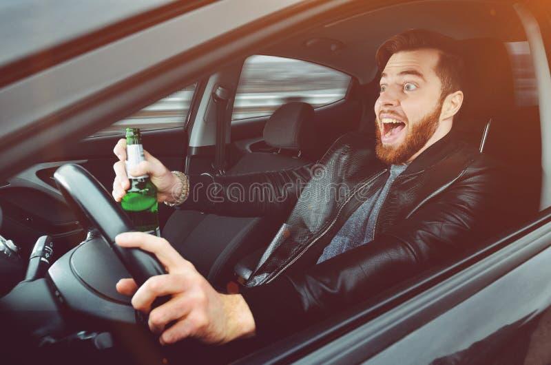 Chmielny mężczyzna jedzie samochód z butelką alkohol w jego ręce Mężczyzna trzyma napędowego koło i butelkę piwo zdjęcie royalty free