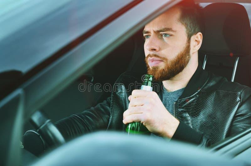 Chmielny mężczyzna jedzie samochód z butelką alkohol w jego ręce Mężczyzna trzyma napędowego koło i butelkę piwo zdjęcia royalty free