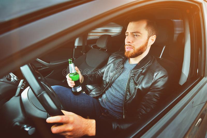 Chmielny mężczyzna jedzie samochód z butelką alkohol w jego ręce Mężczyzna trzyma napędowego koło i butelkę piwo zdjęcie stock