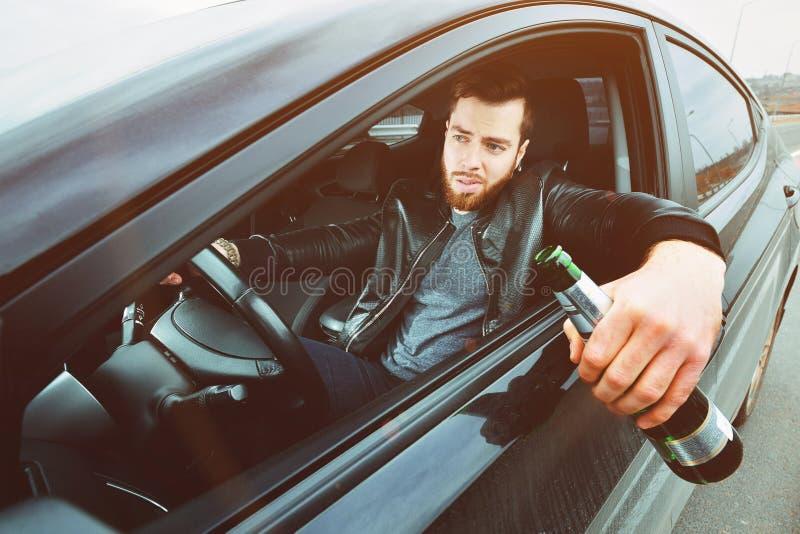 Chmielny mężczyzna jedzie samochód z butelką alkohol w jego ręce Mężczyzna trzyma napędowego koło i butelkę piwo obraz royalty free