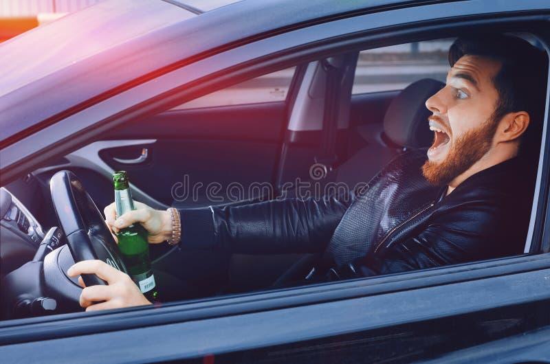 Chmielny mężczyzna jedzie samochód z butelką alkohol w jego ręce Mężczyzna trzyma napędowego koło i butelkę piwo zdjęcia stock