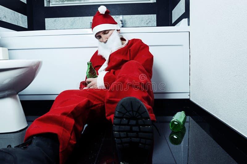 Chmielny Santa Claus dosypianie przy łazienką z piwną butelką w ręce obraz stock