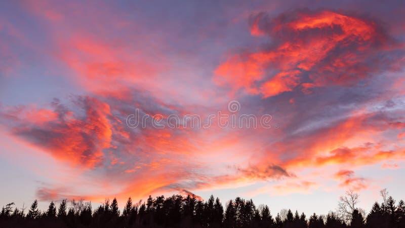 Chmur czerwony pomarańczowy błękitne i fiołkowy koloru zmierzchu nieba dramatyczny tło obrazy stock