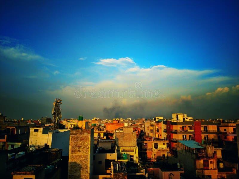 Chmurniejący niebieskie niebo nad miastem zdjęcie stock