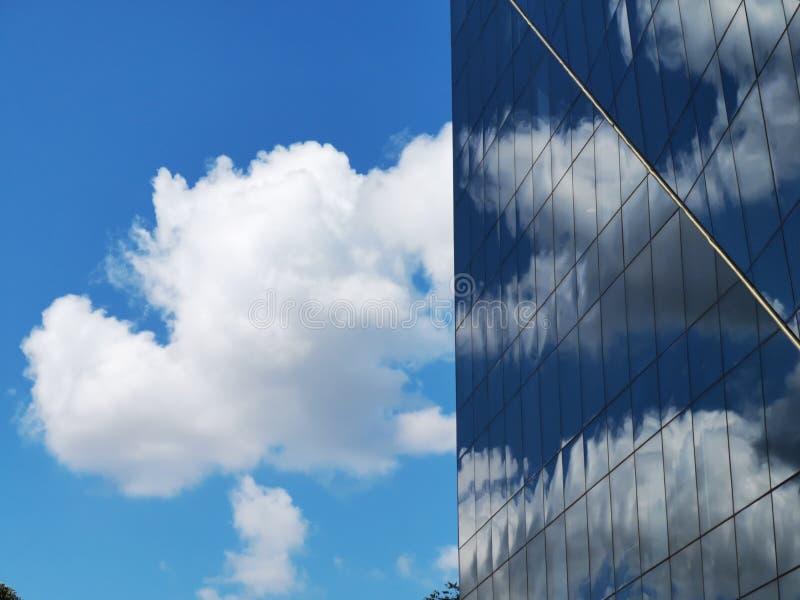 Chmury odbijać na nowożytnym budynku biurowym zdjęcia stock