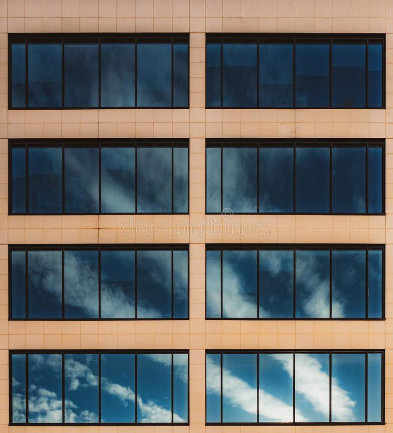 Chmury odbijać w okno budynek biurowy zdjęcie stock