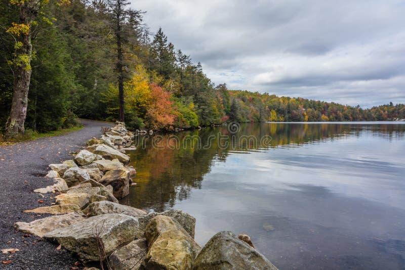 Chmury odbijają w spokojnym Minnewaska jeziorze w orange countym, NY, otaczający jaskrawym spadku ulistnieniem na częsciowo chmur zdjęcie royalty free