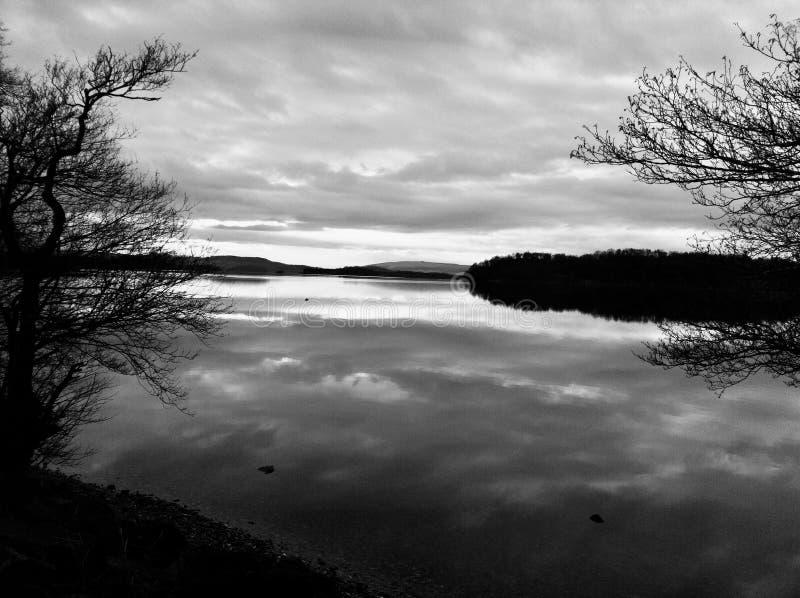 Chmurzy niebo i kształtuje teren widok Loch Lomond zdjęcie royalty free